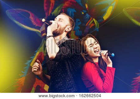 Happy couple singing in karaoke night club