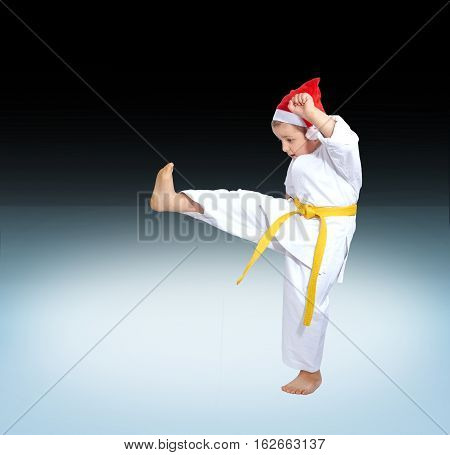 Against the background of the gradient karateka beats kick