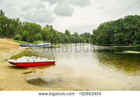 Beautiful landscape of the lake with red-yellow catamaran in the foreground
