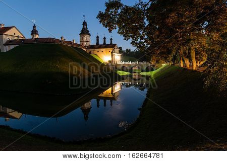Nesvizh, Belarus - August 27, 2016:  Castle in the Belorussian town of Nesvizh with night reflection in moat water