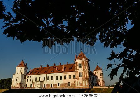 Mir, Belarus - August 28, 2016:  Medieval castle in the Belorussian town of Mir framed by the silhouettes of leaves of trees against the blue sky. The Mir Castle Complex