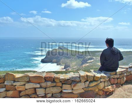 Contemplative Asian young man sitting on the rocks, looking at distance to the blue sea and thinking about something. The Cape Point in South Africa as a background.
