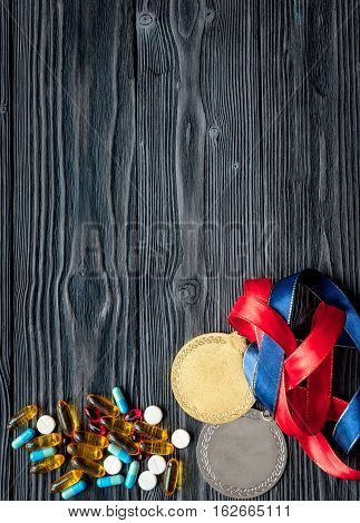 Concept of doping in sport - deprivation medals top view on dark wooden background
