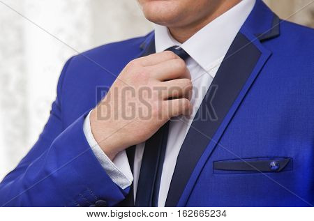 Elegant young fashion man wearing black jacket of formal suit, white shirt and black neck tie. Close up of male hands and shoulders of anonymous person.