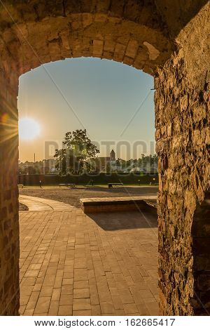 Mir, Belarus - August 28, 2016:  View of the Church of St. Nicholas and the town through the castle entrance in the Belorussian town of Mir illuminated by the rays of the evening sun