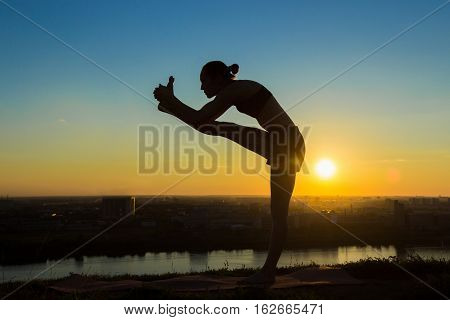 Silhouette of sporty woman practicing yoga in the park at sunset - utthita hasta padangushthasana. Sunset light, golden hour. Freedom, health and yoga concept