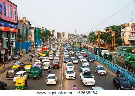 DELHI INDIA - JULY 5 2016: Heavy car traffic in the city center of Delhi India. Buses and construction nearby the road. Various shops cafes restaurants