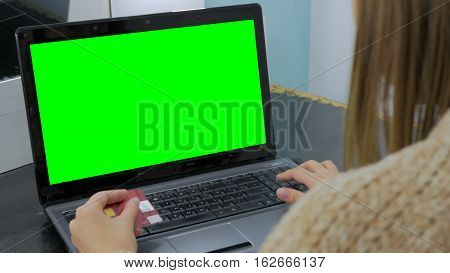 Young woman buying goods from the internet and entering number security code from credit card on laptop with green screen. Online, technology and internet concept.