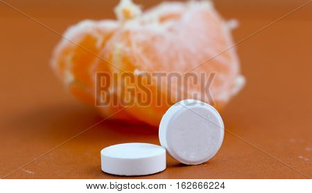 picture of a vitamin c pills and tangerine slicesnatural and artificial vitamins healthy conceptfocus on a pills
