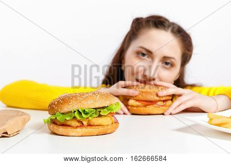 Girl Bites Off A Huge Hamburger. Unhealthy Diets. Young Girl Looks Out From Behind A Hamburger With