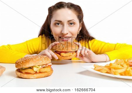 Girl bites off a huge hamburger. Unhealthy diets. Young girl looks out from behind a hamburger with buckles eyes. Unhealthy lifestyle