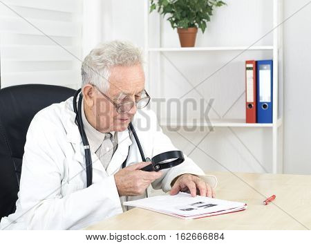 Old doctor with glasses study a literature in consulting room
