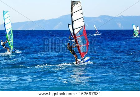 Side view of young windsurfer on background of other windsurfers