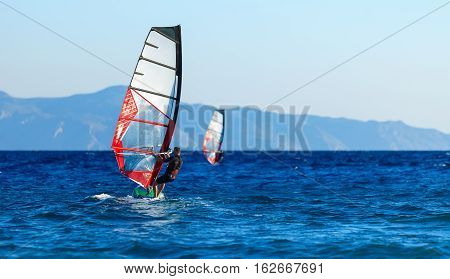 Back view of two windsurfers in action mooving parallel