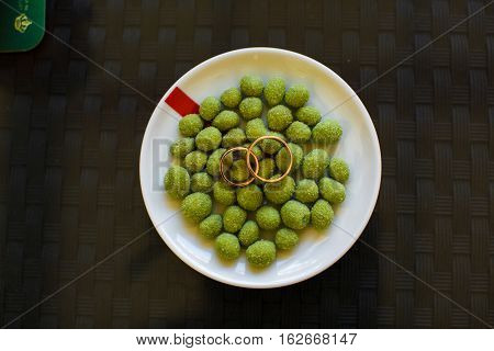 Wedding rings lie on the salty olives
