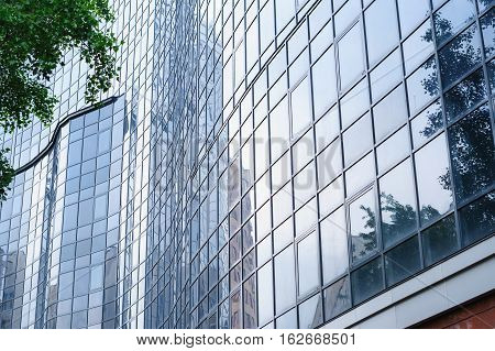 multi-storey office building with glass on sky background
