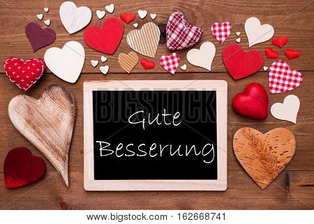 Chalkboard With German Text  Gute Besserung Means Get Well Soon. Many Red Textile Hearts. Wooden Background With Vintage, Rustic Or Retro Style.