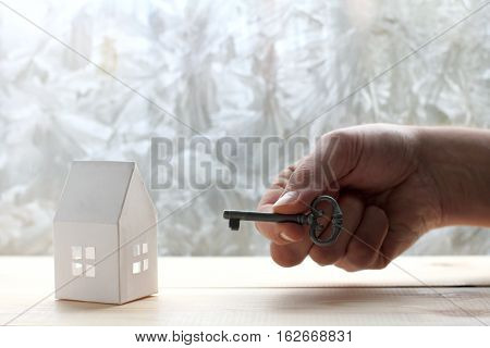 breadboard model the house from a paper and hand with key on a background of the freezing window / effective solutions for all situations