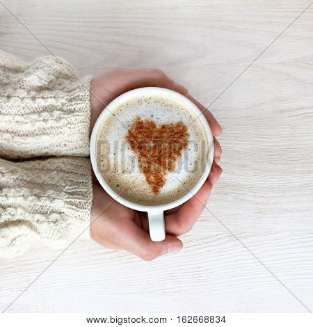 heart symbol decorate frothy cappuccino in a white cup in his hand / favorite coffee with mood