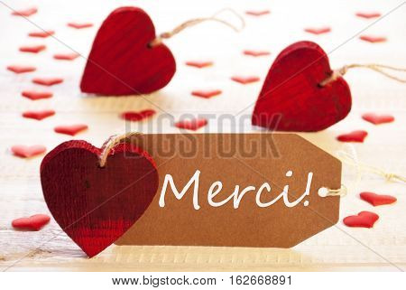 Label With French Text Merci Means Thank You. Many Red Heart. Wooden Rustic Or Vintage Background.