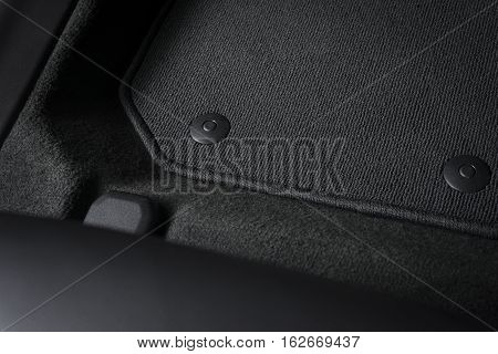 Corner of car mat with floor holder in white car interior