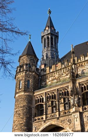Part of the Aachen City Hall with towers and figures against the blue sky , Germany