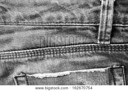 Jeans with seam and pocket background. Jeans texture black and white background. Monochrome denim cloth surface. Jeans back with pocket backdrop. Fashion textile grungy worn jeans closeup image