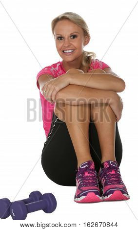 Beautiful smiling blonde woman sitting with lifting weights