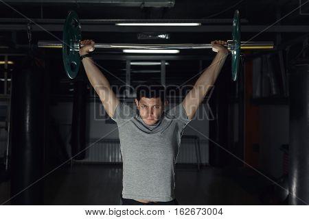 Young Man At Gym Lifting A Barbell.