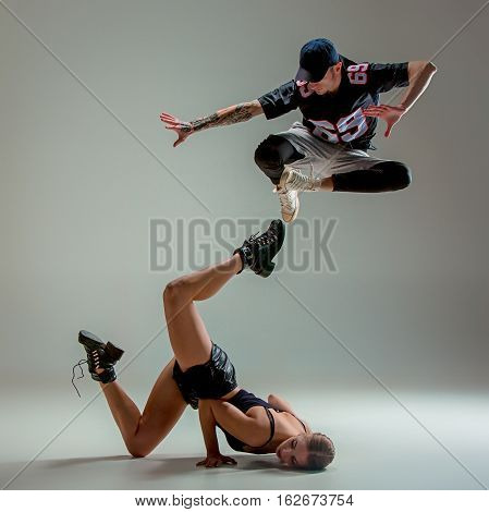 The two young girl and boy dancing hip hop at the gray studio background