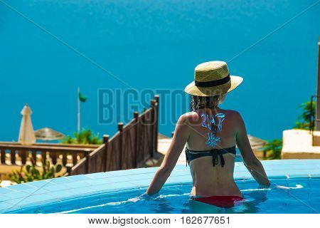 Young slender woman in pool enjoy vacation and looking at Dead Sea. View from behind. 2017 New Travel season concept. Copyspace.