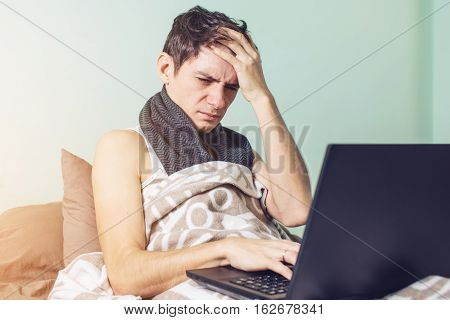 Young Man Sick With A Cold Lying In Bed