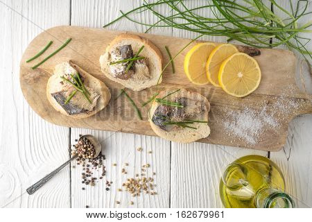 Sandwiches with sardines and onions on a cutting board horizontal