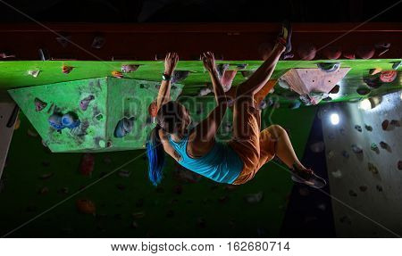 Young woman bouldering along ceiling of indoor climbing gym