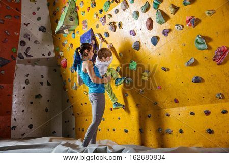 Young female bouldering instructor helping boy climb artificial wall