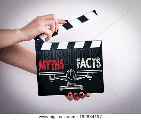 Myths vs Facts Balance. Female hands holding movie clapper.