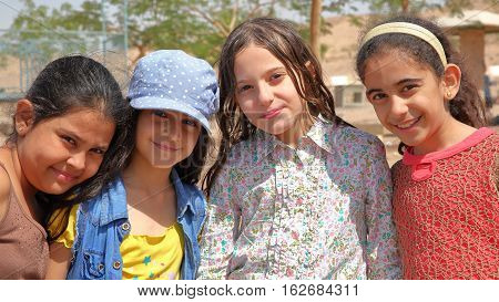 AQABA, JORDAN - MARCH 15, 2016: Portrait of four cute little girls smiling on a beach