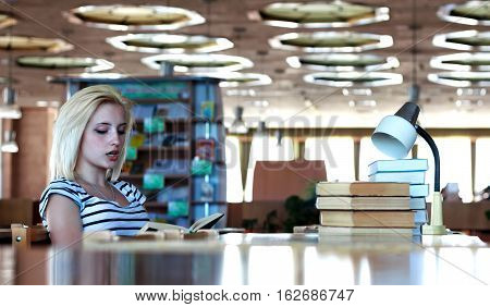 Schoolgirl or student reads aloud the book sitting at a table in the library