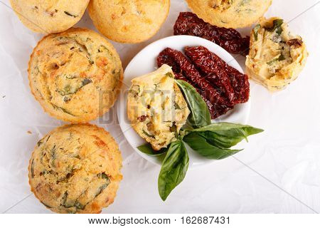 Savory cheese maffins with basil and sun-dried tomato. Top view.