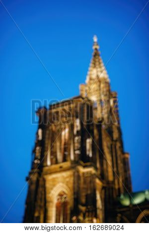 Defocused view of Cathedral of Our Lady (Notre Dame) of Strasbourg at dusk in Strasbourg Alsace France - view from below