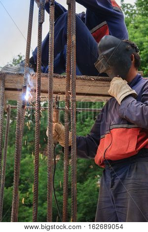 Migrant workers working in construction as a welder