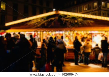 Defocused customers drinking hot wine at the traditional market stall while visiting the oldest Christmas Market worldwide in central Strasbourg Alsace