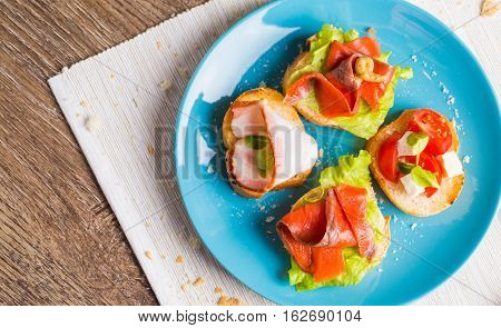 Traditional Italian antipasti bruschetta with salmon and bacon. Flat lay.
