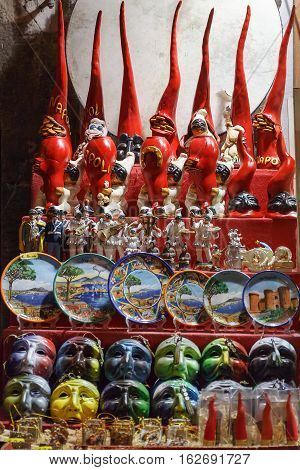 Naples Italy - December 9 2016: San Gregorio Armeno stand of typical Neapolitan items figurines of Pulcinella hand-painted plates masks of Pulcinella the red horn superstitious and charms.
