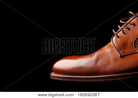 Brown leather derby shoes.Polish for shine on black background