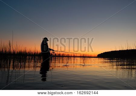 The picture shows a silhouette of a fisherwoman..The fisherwoman stands in the water and catch fish. Rod is horizontal. Fisherman waiting for the fish bite.