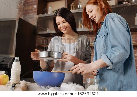 Always smile. Two friendly women wearing casual clothes sifting flour for pastry standing in semi position in the kitchen