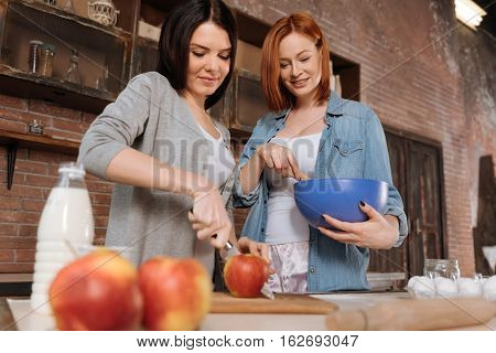 Be carefull. Attractive smiling woman standing at the table holding wooden spoon and big blue plate while mixing, looking at her friend that is slicing big red apple