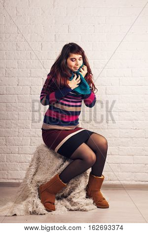 Cheerful brunette young woman in scarf indoors