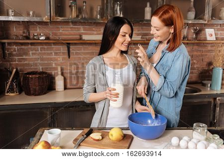 Enjoying weekend. Young pretty brunette holding a bottle of milk looking at finger of her friend that put sign on her nose using flour